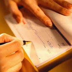 Fotografía de un hombre firmando un cheque en referencia a las ventajas del pagaré