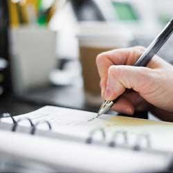 La imagen muestra una libreta y una mano con un bolígrafo anotando en ella en relación con los administradores de la empresa