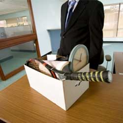Imagen en la que aparece una fotografía de un trabajador en su despacho y junto a él una caja con todas sus pertenencias en relación con las alternativas al despido del trabajador