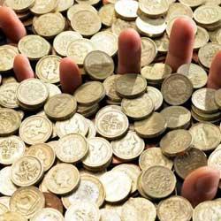 La imagen muestra una fotografía de un monton de monedas de las que salen los dedos de unas manos en referencia al alzamiento de bienes