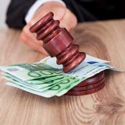 Fotografía de un juez golpeando un juez con el mazo varios billetes de cien euros en relación con las costas judiciales