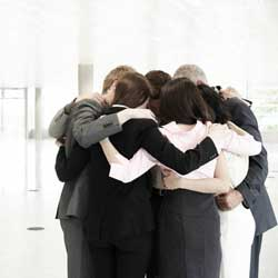 La imagen muestra una fotografía de un grupo de empleados hablando en corro y formando un círculo en relación con el expediente de regulación  de empleo o ERE
