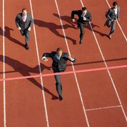 Fotografía de un grupo de empresarios llegando a la meta de una pista de atletismo en una carrera en referencia a la nueva ley de defensa de la competencia