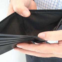 Fotografía de un hombre abriendo su cartera, la cual, está vacía. La imagen tiene relación con la prevención de la morosidad empresarial