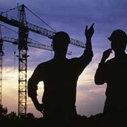 Fotografía de la sirueta de dos obreros y al fondo las siruetas de unas gruas en relación con la Ley de ordenación de la edificación