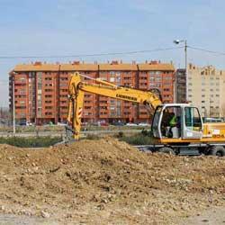 La imagen muestra una fotografía de una máquina escabadora trabajando el suelo de unas obras en relación con la nueva ley estatal del suelo