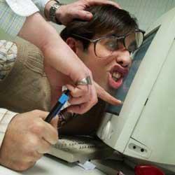 Fotografía de una persona que está siendo acosada en el trabajo de forma que otra persona está empujando la cabeza de este contra un ordenado. Esta fotografía está relacionada con el nuevo fenómeno llamado mobbing