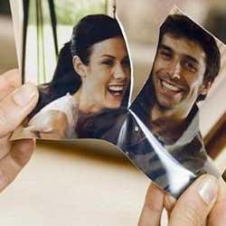 La imagen muestra una fotografía de unas manos que sujetan una foto de una pareja rota en dos trozos en relación con las relaciones personales y patrimoniales de las parejas de hecho