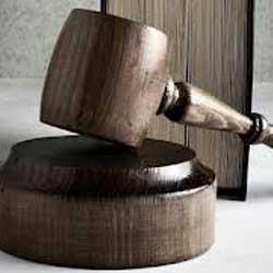 La imagen muestra una fotografía del mazo de madera de un juez y tras él un libro. La imagen hace referencia al seguro de defensa jurídica