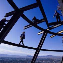 Fotografía de unos obreros subidos a unos andamios. La imagen tiene referencia con la subcontratación en el sector de la construcción