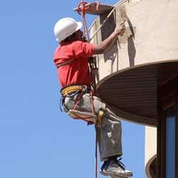 Fotografía de un obrero trabajando en lo alto de un edificio del que cuelga mediante cuerdas en relación con los casos de accidente laboral