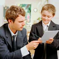 La imagen muestra a un empresario vestido de traje junto a su hijo que viste de igual forma mientras los dos analizan unos papeles sobre la empresa familiar