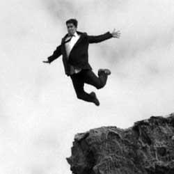 La imagen muestra una fotografía en blanco y negro de un empresario saltando de un acantilado en relación con la prestación de desempleo para trabajadores autónomos