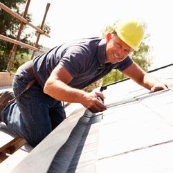 Un albañil trabajando en el tejado de una casa en relación con las contingencias profesionales para las empresas que disminullan en riesgo laboral