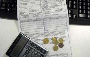 Fotografía de una multa de tráfico sobre una mesa, y sobre la multa se observa una calculadora y unas cuantas modenas de céntimo de euro. Bajo la multa aparece un telado de ordenador. La imagen es referente a la notificación de las multas de tráfico