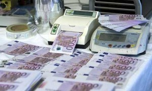 La imagen muestra una fotografía de una máquinas para contar billetes, de las cuales salen multitud de billetes de quinientos euros. La imagen está relacionada con las medidas en las operaciones vinculadas para evitar el fraude fiscal