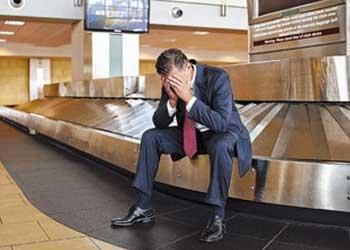 Fotografía de un hombre vestido de chaqueta que ha perdido el equipaje en un aeropuerto y se encuentra sentado sobre la pasarela de maletas con las manos en la cabeza mientras se lamenta de la pérdida