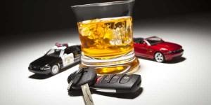 Imagen en la que aparece un vaso que contiene alguna bebida alcohólica y junto a él las llaves de un coche y dos coches en miniatura. Uno de un particular y otro de la policía. La imagen está relacionada con la prueba de alcoholemia