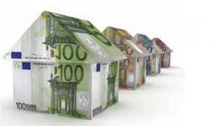 La imagen muestra una fila de casas fabricadas con billetes de euro. La imagen está relacionada con la deducción de la vivienda