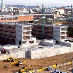 Fotografía de unas obras de unos edificios en donde trabajan obreros. La imagen está relacionada con la extinción de contratos por la reforma laboral