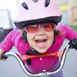 La imagen muestra a una niña con un casco y gafas de sol subida en una bicicleta en relación con los principales cambios en la nueva ley de tráfico