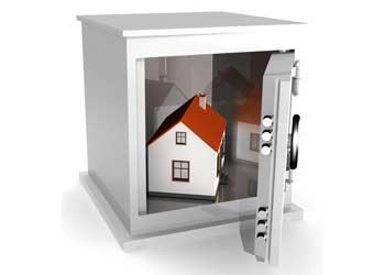 La imagen muestra una caja fuerte que contiene en su interior una casa en miniatura en relación con el seguro de alquiler