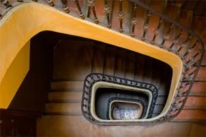 Fotografía de las escaleras de un edificio de viviendas vistas desde arriba. La imagen está vinculada a los gastos de comunidad y los impagos por parte de sus habitantes