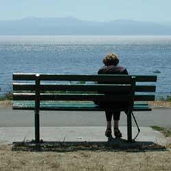 Fotografía de una anciana sentada en un banco sóla frente a la playa. La imagen tiene referencia con la pensión de viudedad