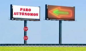 """La imagen muestra dos vallas publicitarias. En la de la derecha aparace una gran flecha que señala hacia la otra valla publicitaria, en la que está escrito """"paro autónomos"""". Bajo esta valla aparecen dos señales de tráfico de STOP en relación con la prestación de desempleo para autónomos"""