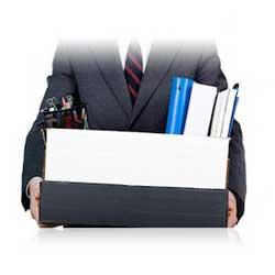 Fotografía de un hombre vestido de chaqueta y corbata con unas cajas en sus manos en referencia al despido y la indemnización de los trabajadores