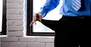 Fotografía de la parte del cuerpo de un hombre vestido de traje en la que se muestra su mano vaciando su bolsillo vacio en relación con los impagos del deudor o de los morosos