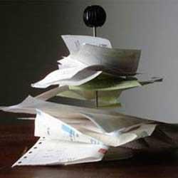La imagen muestra una fotografía de varias facturas acumuladas desordenadamente y pinchadas por un palo que las acumula. La imagen tiene relevancia con las sanciones por realizar una facturación irregular