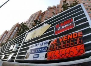 La imagen muestra una fotografía de una valla de metal donde se anuncian varios carteles de alquiler y compra de viviendas. Tras esta valla asoman unos edificios