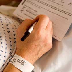 La imagen muestra una fotografía en la que aparece una persona firmando un contrato en referencia al consentimiento informado en la práctica médica