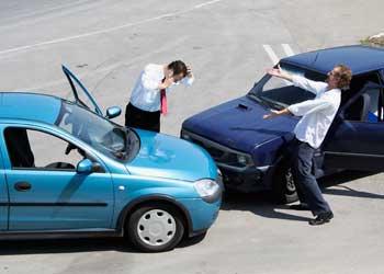 Fotografía de un accidente de dos coches que han chocado frontalmente. Los conductores se encuentran discutiendo fuera de sus vehículos. La imagen guarda relación con la indemnización por accidente de tráfico