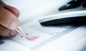 Fotografía de la mano de un hombre que sujeta un bolígrafo y escribe sobre unas facturas del IVA. A su lado aparece un teléfono