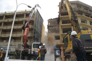 Demolición a un edificio de la ciudad de Granada en la que aparecen varios obreros y dos grúas destruyendo el edificio