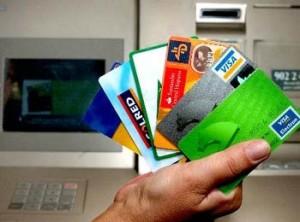 Fotografía en la que aparece una mano llena de tarjetas de crédito y de fondo un cajero automático