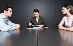 Fotografía de una pareja separada sentados en una mesa cada uno a un lado de ella. En el medio de la mesa aparece una mujer mediadora que regula la pensión de alimentos impuesta por el juez