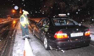 Fotografía de un Guardia Civil parando a un vehículo BMW negro mientras nieva