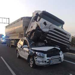 La imagen muestra una fotografía de un accidente de camión en el que este se encuentra aplastando un vehículo todoterreno en la autovía