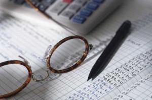 Fotografía de unos papales que muestran datos numéricos y unas gafas, calculadora y bolígrafo sobre ellos. La imagen está relacionada con el derecho de los ciudadanos a recurrir a la administración