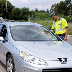 La imagen muestra una fotografía de un guardia civil realizando un control de los puntos del carnet de conducir