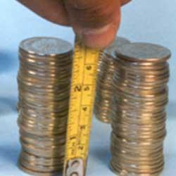 Fotografía de unas monedas colocadas unas sobre otras y una mano con una regla midiendolas en referencia a los intereses moratorios
