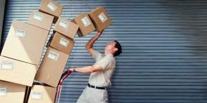 Fotografía de un empleado transportando unas cajas que se les cae encima. La imagen está relacionada con los riesgos laborales en la actividad empresarial