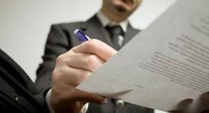 Fotografía en un ángulo contrapicado de un empresario realizando una firma en un documento