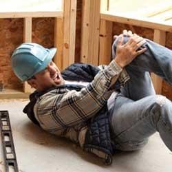 Fotografía de un obrero lesionado en el lugar de trabajo que está tirado en el suelo y sujetando su rodilla izquierda con sus manos mientras expresa dolor en su cara. La imagen está relacionada con el recargo de las prestaciones en un accidente de trabajo