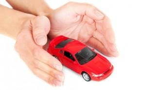 Fotografía de unas manos que protejen un coche rojo en miniatura en relación con el seguro voluntario en accidentes de tráfico