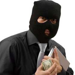 Fotografía de un hombre enmascarado con un pasamontañas y que sujeta en sus manos un ordenador y un puñado de billetes simulando realizar una estafa