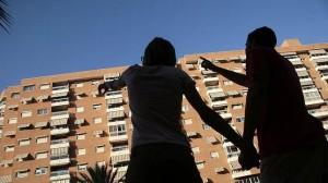 Fotografía de una pareja mirando desde la calle un piso de un edificio. La fotografía tiene relación con el pago de la hipoteca a medias tras un divorcio